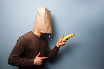 Young man with bag over his head using banana as gun