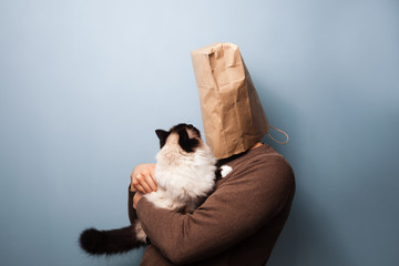Young man with bag over head holding his cat