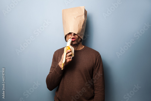 Young man with bag over head eating banana