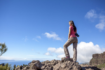 young woman on top of a mountain enjoying the view