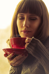 Girl Drinking Coffee  with Steam. Warm color toned