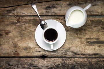 Coffee. Cup of Coffee with Milk Jug on Wood Background. Top View