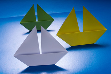 Group of Paper Boats Sailing on Blue paper sea. Origami Ship