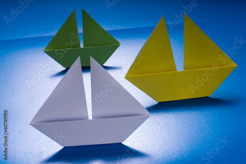 canvas print picture Group of Paper Boats Sailing on Blue paper sea. Origami Ship