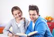 Zwei lachende Studenten lesen in einem Buch