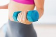 Mid section of a woman lifting dumbbell weight in gym