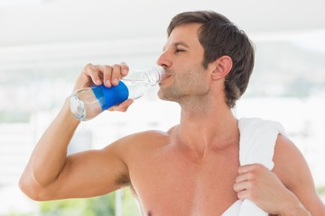 Shirtless man with towel drinking water