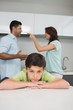 Closeup portrait of sad son while parents quarreling