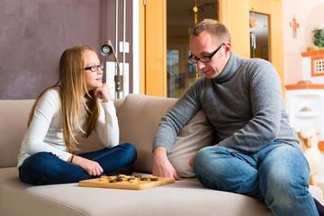 Vater und Tochter spielen das Spiel Dame