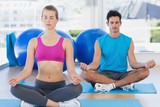 Couple sitting in lotus posture and eyes closed at fitness studi
