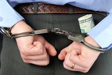 Man's hands in handcuffs with money in his pocket