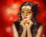 Young beautiful woman in golden carnival mask.