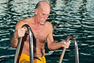 Senior man walking out of swimming pool. Wearing yellow swimming