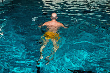 Healthy senior man with beard in indoor swimming pool. Rear view