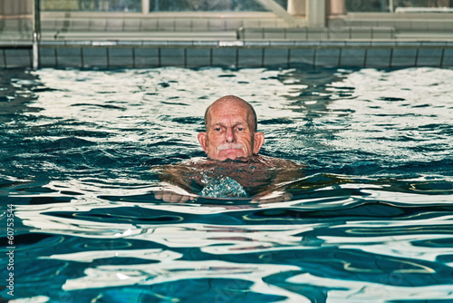 Healthy senior man with beard in indoor swimming pool.