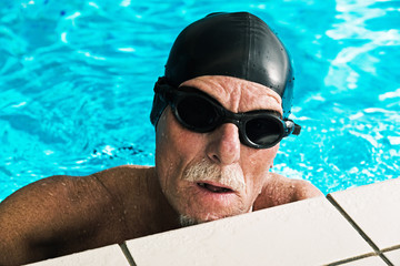 Active healthy senior man with beard in swimming pool wearing bl