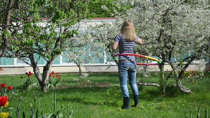 woman spin hula hoop ring in spring garden. fitnes at home.