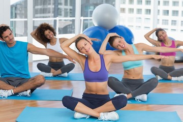 People with trainer doing pilate exercises