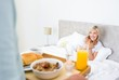 Happy woman sitting in bed with breakfast in foreground