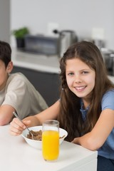 Portrait of two smiling siblings enjoying breakfast