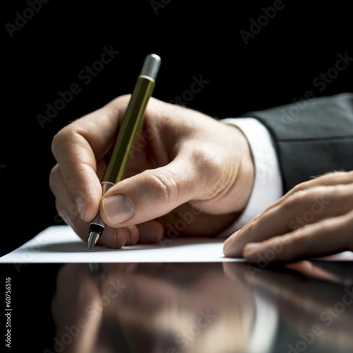 Businessman writing on a sheet of white paper