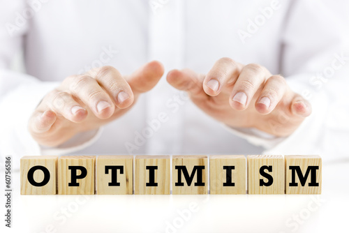 Man shielding the word Optimism with his hands