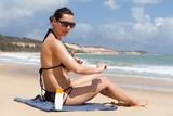 Frau benutzt Sonnencreme am Strand