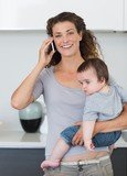Happy woman answering smartphone while carrying baby