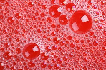 Texture of soap bubbles on red background close-up. macro