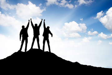 Silhouette of a team on the mountain top. Active life concept