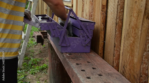 worker from purple tool boxes take centimeter hammer spike bags