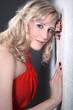 Hübsche blonde Frau blickt an der Wand