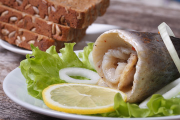 pickled herring roll with onion on lettuce, lemon and bread