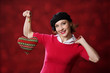 Funny girl with knitted heart at light background