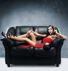 A woman in a red dress with a telephone on a leather sofa