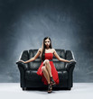 A glamour woman in a red dress sitting on a black leather sofa