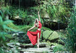 A beautiful ballerina in a red dress dancing in the forest