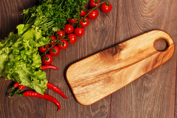 Cutting board and vegetables on a wooden background