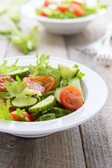 Vegatable salad from fresh cucumbers, lettuce and cherry tomatoe