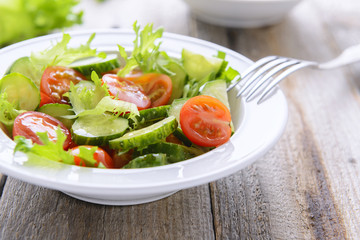 Fresh salad from cucumbers and tomatoes on white plate