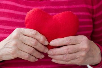 Heart in hand of elderly woman