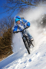 Cyclist riding on a mountain bike in the snow winter forest