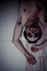 Crime scene, man with blood stains, nude with gas mask
