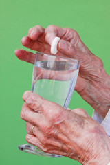 Senior woman ready to dissolve her pill in water