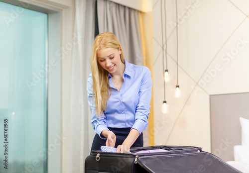 businesswoman packing things in suitcase
