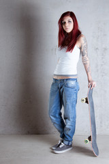 Woman with skateboard portrait against concrete wall.