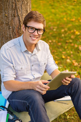 smiling male student in eyeglasses with tablet pc