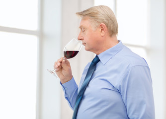 older man smelling red wine