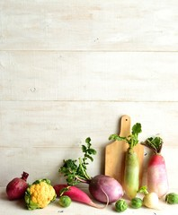 Colorful spring root vegetables with cutting board