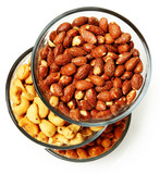 Three glass bowls filled with cashews, salted roasted almonds an
